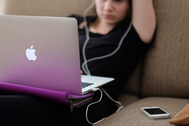 photo of young woman sitting with laptop